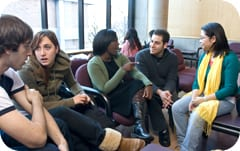 A group of students sitting on sofas, engaged in conversation with one another.