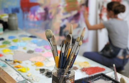 Paintbrushes are in the foreground as an artist paints in the background