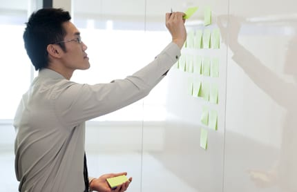 A man strategically places and looks through sticky-notes on a white board