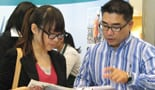 A company representative speaking to a student at a career fair
