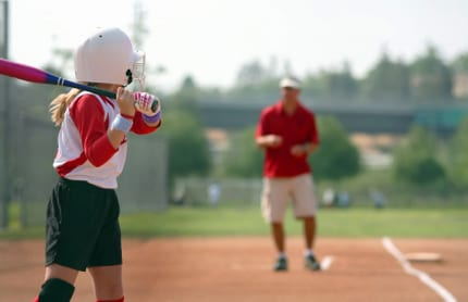 A child playing baseball with an adult giving instruction in the background
